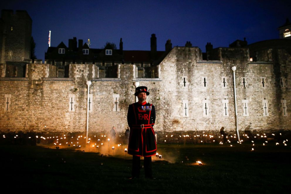 PHOTO: A Yeoman of the Guard stands among lit torches that are part of the installation Beyond the Deepening Shadow at the Tower of London, in London, Nov. 4, 2018.