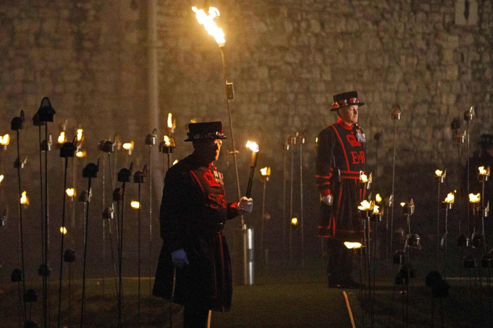 PHOTO: Yeoman Warders, commonly known as a Beefeaters, stand by after lighting the first of thousands of flames in a lighting ceremony at the Tower of London, Nov. 4, 2018.