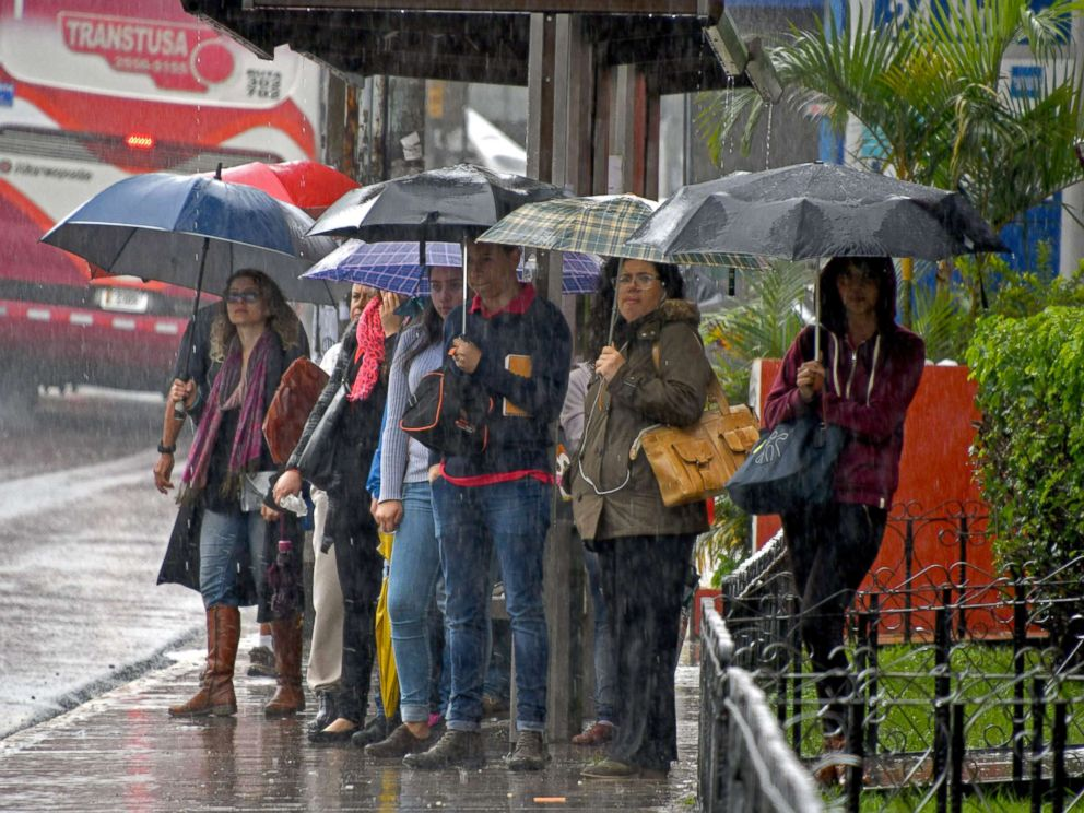PHOTO: Locals holding umbrellas wait at a bus stop during a downpour caused by tropical storm Nate in Cartago, Costa Rica, Oct. 5, 2017.