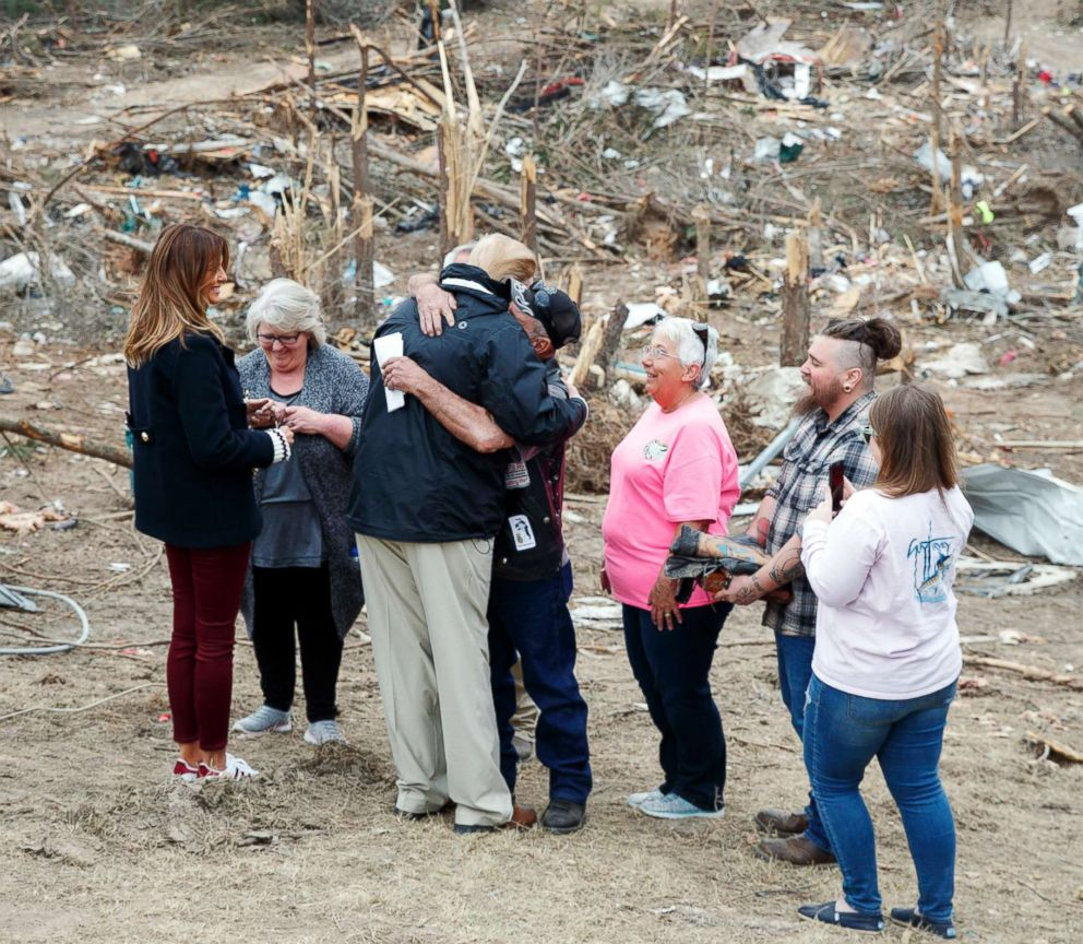 President Donald Trump hugs a resident as he and first lady Melania Trump talk with people in Beauregard, Ala., as they travel to tour areas where tornadoes killed 23 people in Lee County, Ala., March 8, 2019.