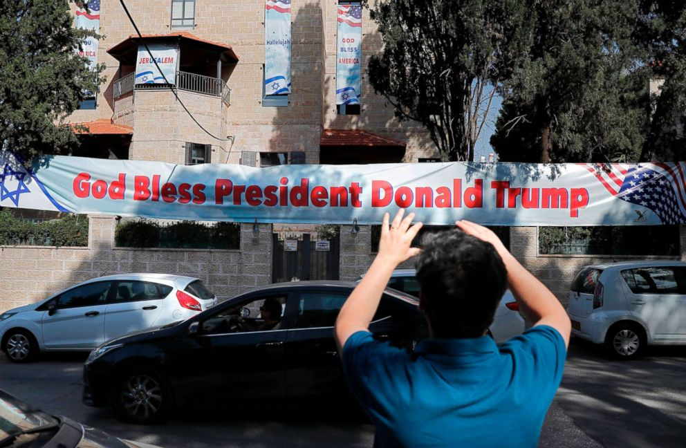 PHOTO: An Israeli man takes a picture, May 11, 2018, of a poster placed near the compound of the US consulate in Jerusalem, which will host the new US embassy, as posters praising the US president hang in the street.
