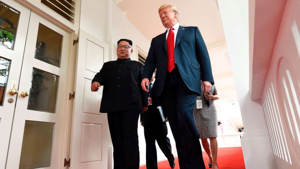 North Korea's leader Kim Jong Un walks with President Donald Trump at the start of their summit, at the Capella Hotel on Sentosa island, in Singapore, on June 12, 2018.
