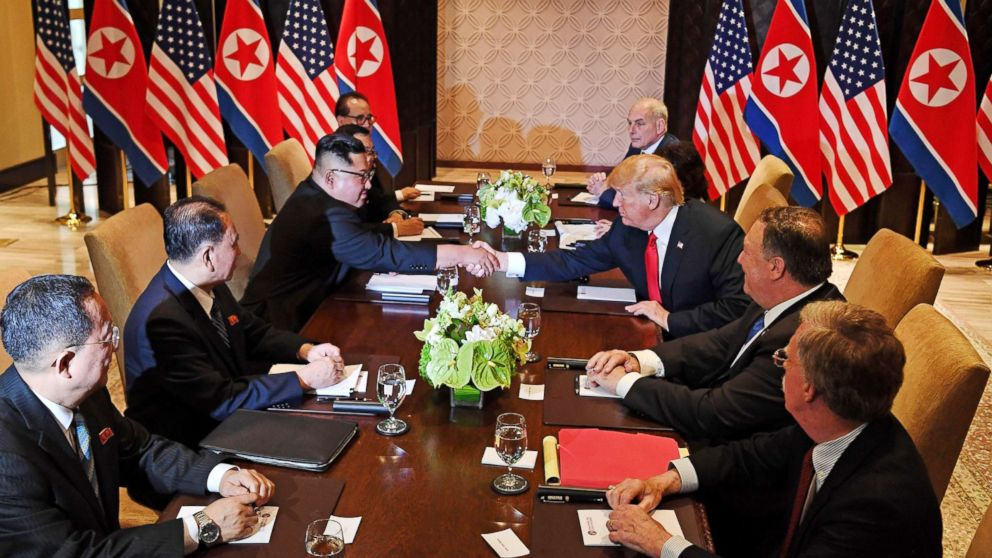 President Donald Trump shakes hands with North Korea's leader Kim Jong Un as they sit down with their respective delegations for the U.S.-North Korea summit, at the Capella Hotel on Sentosa island in Singapore on June 12, 2018.