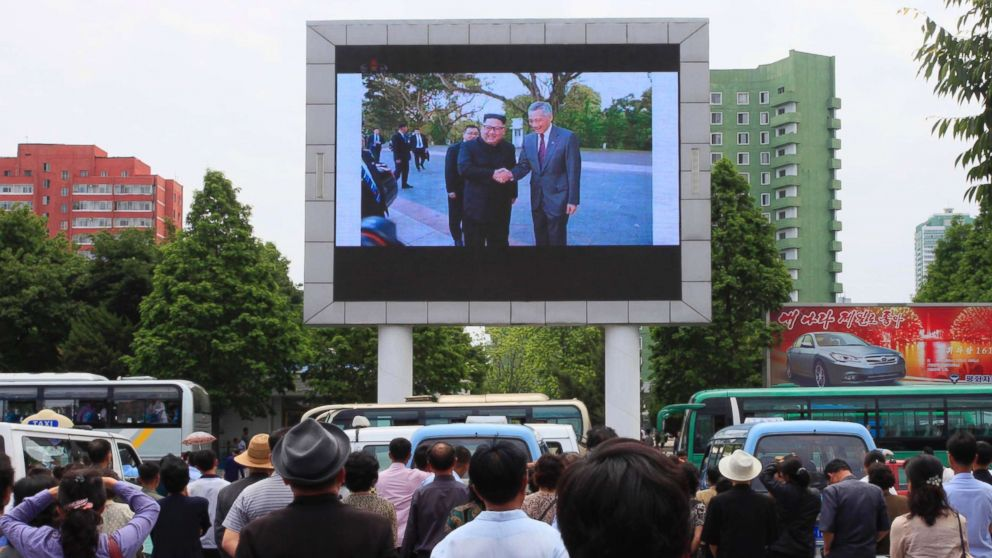 People watch a large screen at the main train station airing video of North Korean leader Kim Jong Un shaking hands with Singapore Prime Minister Lee Hsien Loong during his trip to Singapore in Pyongyang, North Korea, June 11, 2018.