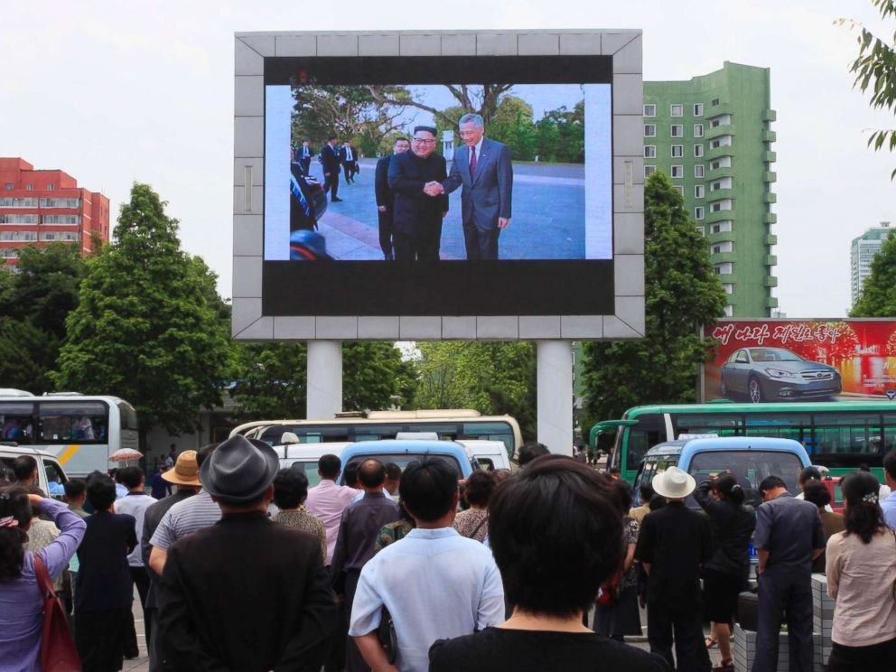PHOTO: People watch a large screen at the main train station airing video of North Korean leader Kim Jong Un shaking hands with Singapore Prime Minister Lee Hsien Loong during his trip to Singapore in Pyongyang, North Korea, June 11, 2018.