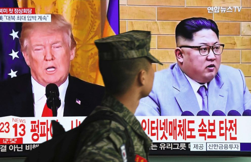 PHOTO: A South Korean soldier walks past a television screen showing pictures of President Donald Trump and North Korean leader Kim Jong Un at a railway station in Seoul on March 9, 2018.