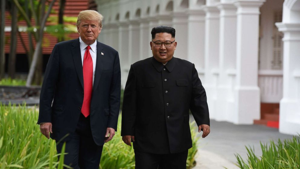 President Donald Trump walks with North Korea's leader Kim Jong Un during a break in talks at their summit, at the Capella Hotel on Sentosa island in Singapore on June 12, 2018.