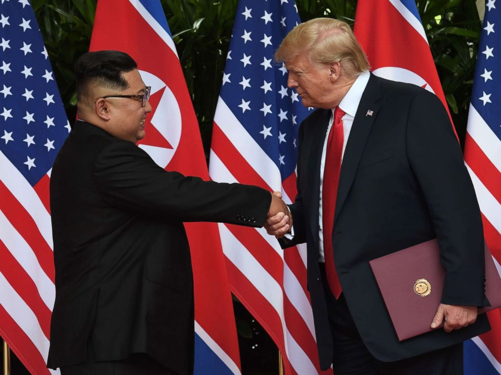 PHOTO: North Koreas leader Kim Jong Un shakes hands with President Donald Trump after taking part in a signing ceremony at the end of their summit at the Capella Hotel on Sentosa island in Singapore on June 12, 2018.