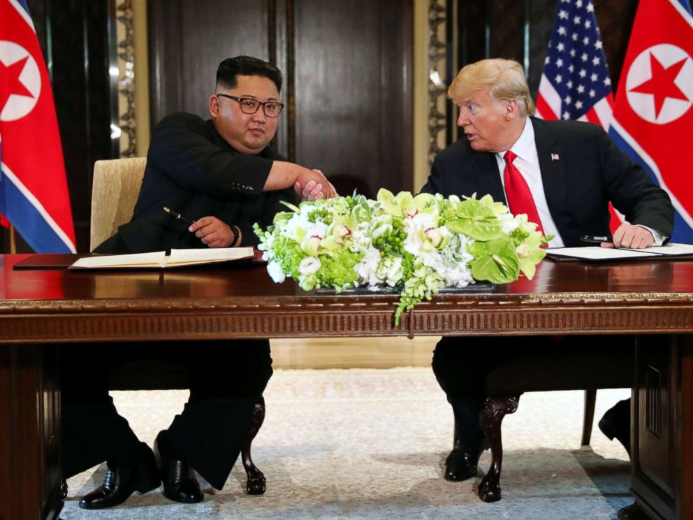 PHOTO: President Donald Trump shakes hands with North Koreas leader Kim Jong Un after signing documents after their summit at the Capella Hotel on Sentosa island in Singapore June 12, 2018.