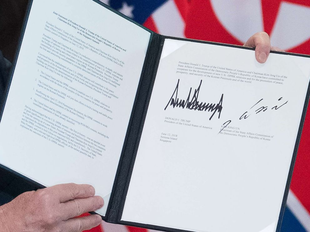 PHOTO: President Donald Trump holds up a document signed by him and North Koreas leader Kim Jong Un following a signing ceremony at the Capella Hotel on Sentosa island in Singapore on June 12, 2018.