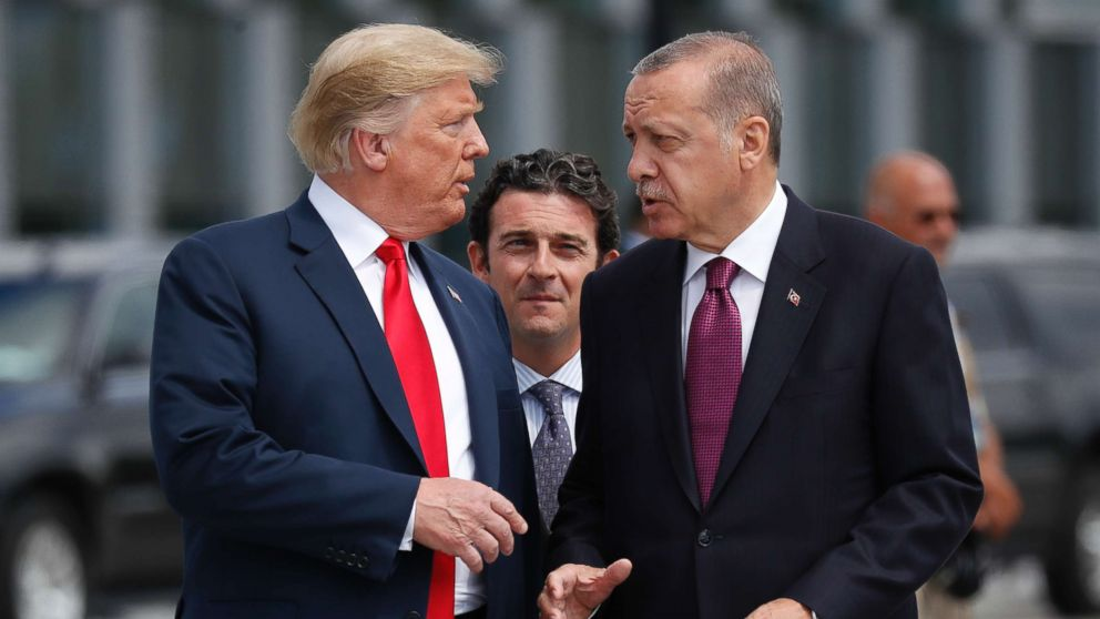 President Donald Trump talks with Turkey's President Recep Tayyip Erdogan as they arrive together for a family photo at a summit of heads of state and government at NATO headquarters in Brussels, July 11, 2018.