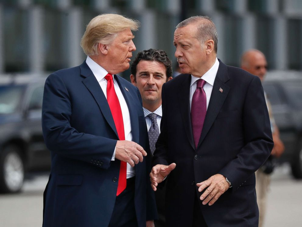 PHOTO: President Donald Trump talks with Turkeys President Recep Tayyip Erdogan as they arrive together for a family photo at a summit of heads of state and government at NATO headquarters in Brussels, July 11, 2018.