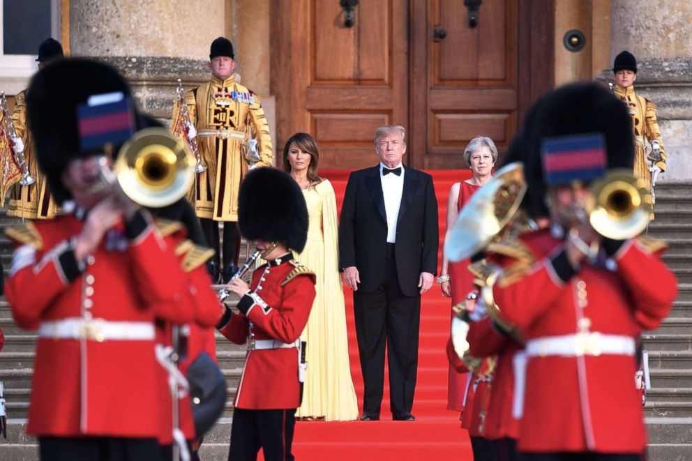 PHOTO: Britains Prime Minister Theresa May (R) President Donald Trump and his wife First Lady Melania Trump stand on steps in the Great Court watching and listening to bands perform a ceremonial welcome at Blenheim Palace, west of London, July 12, 2018.