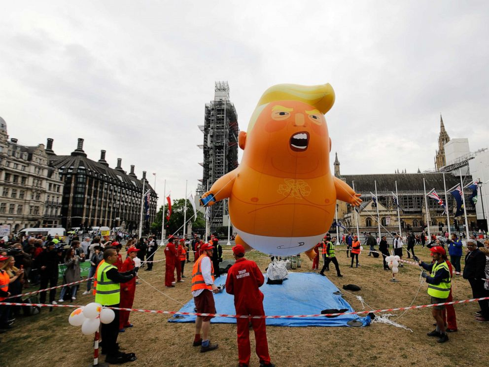 PHOTO: Anti-Trump demonstrators inflate a giant balloon depicting US President Donald Trump as an orange baby in Parliament Square in London on June 4, 2019.