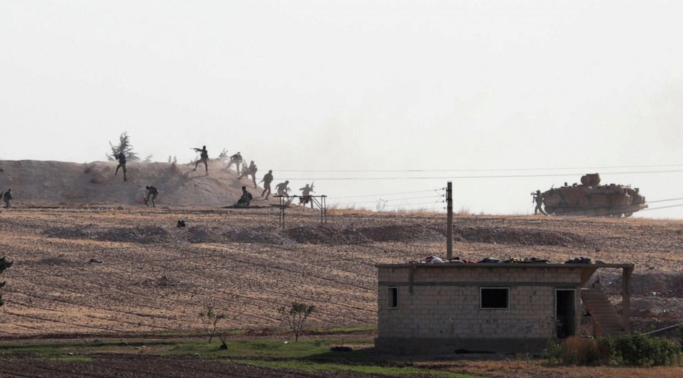 PHOTO: Turkey-backed Syrian rebel fighters are seen in action in the village of Yabisa, near the Turkish-Syrian border, Syria, Oct. 13, 2019.