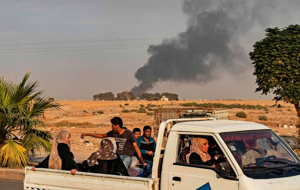 PHOTO: Civilians ride a pickup truck as smoke billows following Turkish bombardment in the northeastern town of Ras al-Ain in Syrias Hasakeh province along the Turkish border on Oct. 9, 2019.