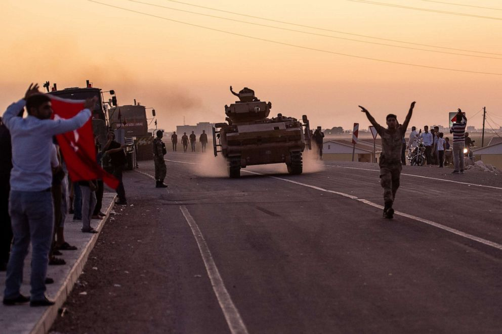 PHOTO: People wave as Turkish soldiers prepare to cross the border into Syria on Oct. 9, 2019, in Akcakale, Turkey.