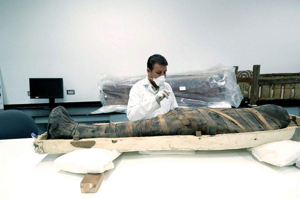 PHOTO: An Egyptian archaeologist checks the mummy during restoration work on the coffin of King Tutankhamun at the conservation center in the Grand Egyptian Museum, Aug. 4, 2019.