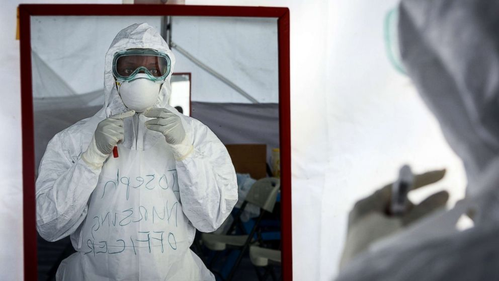 A member of the medical staff of the Ebola Treatment Unit (ETU) checks her Personal Protective Equipment (PPE) in front of the mirror during a weekly rehearsal at the Bwera General Hospital in Bwera, western Uganda, Dec. 12, 2018. The second largest Ebola outbreak in Africa has started in Democratic Republic of Congo causing 298 deaths since August 2018, according to the World Health Organization.