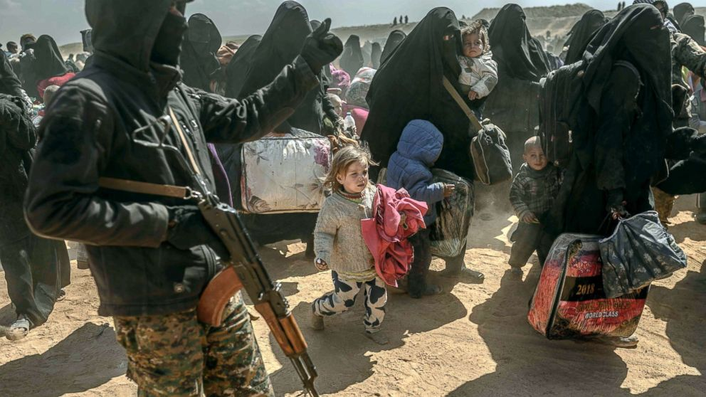 Women and children, evacuated from the Islamic State group's embattled holdout of Baghouz, arrive at a screening area held by the US-backed Kurdish-led Syrian Democratic Forces in Deir Ezzor, Syria, March 6, 2019. Veiled women carrying babies and wounded men on crutches hobbled out of the jihadist village after US-backed forces pummeled the besieged enclave.