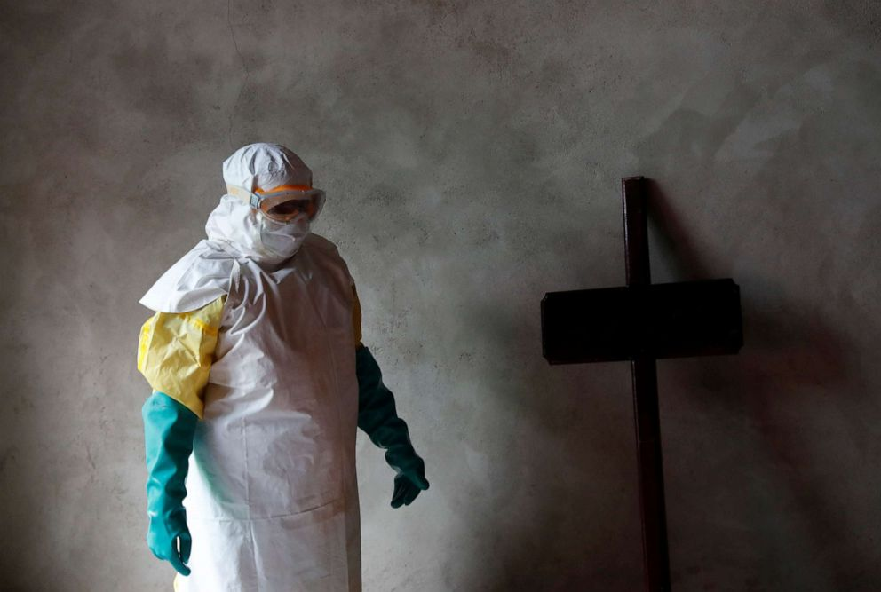 PHOTO: A healthcare worker stands next to a cross during a funeral for Kavugho Cindi Dorcas, who is suspected of dying of Ebola in Beni, North Kivu Province of the Democratic Republic of Congo, Dec. 9, 2018.