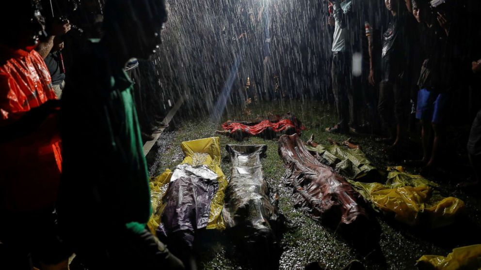 People gather in the rain around bodies of Rohingya refugees after their boat capsized off the Inani beach near Cox's Bazar, Bangladesh, Sept. 28, 2017.