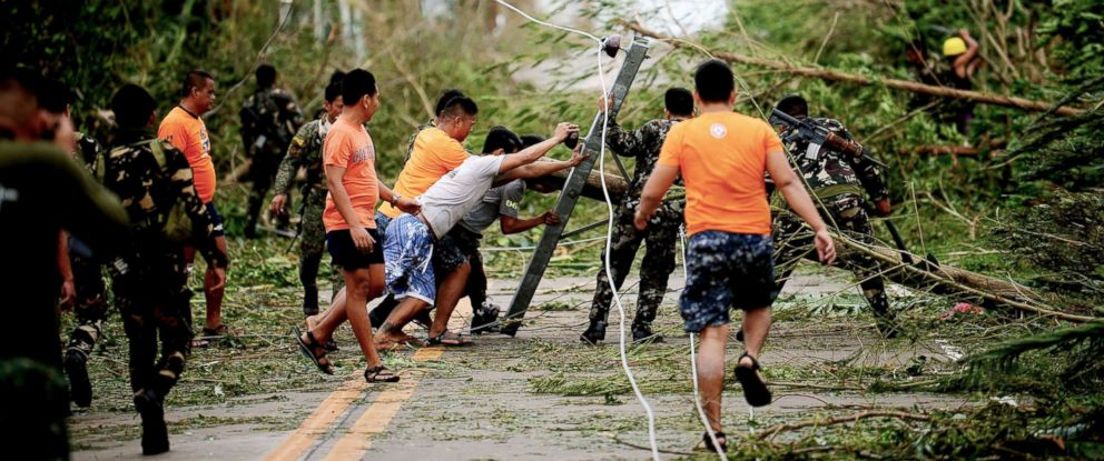 PHOTO: Rescue workers clear a road of debris and toppled electric posts caused by strong winds due to super Typhoon Mangkhut as they try to reach Baggao town, north of Manila, Philippines, Sept. 15, 2018.