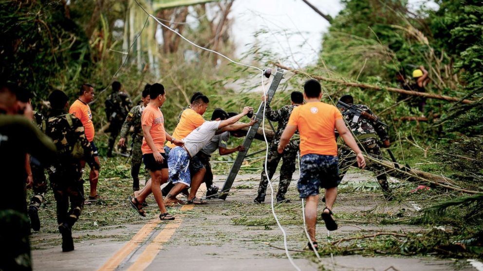 Rescue workers clear a road of debris and toppled electric posts caused by strong winds due to super Typhoon Mangkhut as they try to reach Baggao town, north of Manila, Philippines, Sept. 15, 2018.