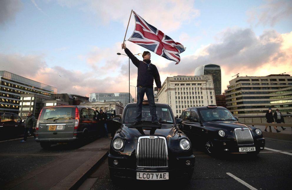 PHOTO: A black cab driver waves a Union flag while standing on a taxi as black cab drivers take part in a protest against Transport for London and Uber, in London, Jan. 18, 2018.  Uber ban reversed in London, allowing the ride-sharing app to operate uber london cab protest ap ps 180626 hpEmbed 23x15 992