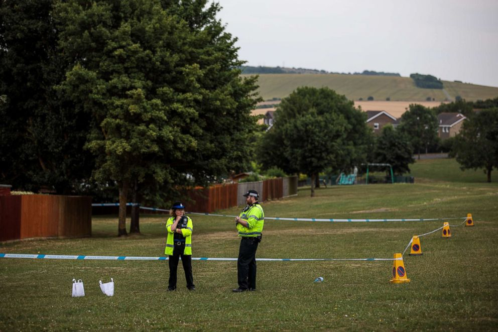 Police officers stand at a cordon around an area of grass near to Amesbury Baptist Centre as Wiltshire Police declare a major incident after a man and woman were exposed to an unknown substance, July 4, 2018, in Amesbury, England.