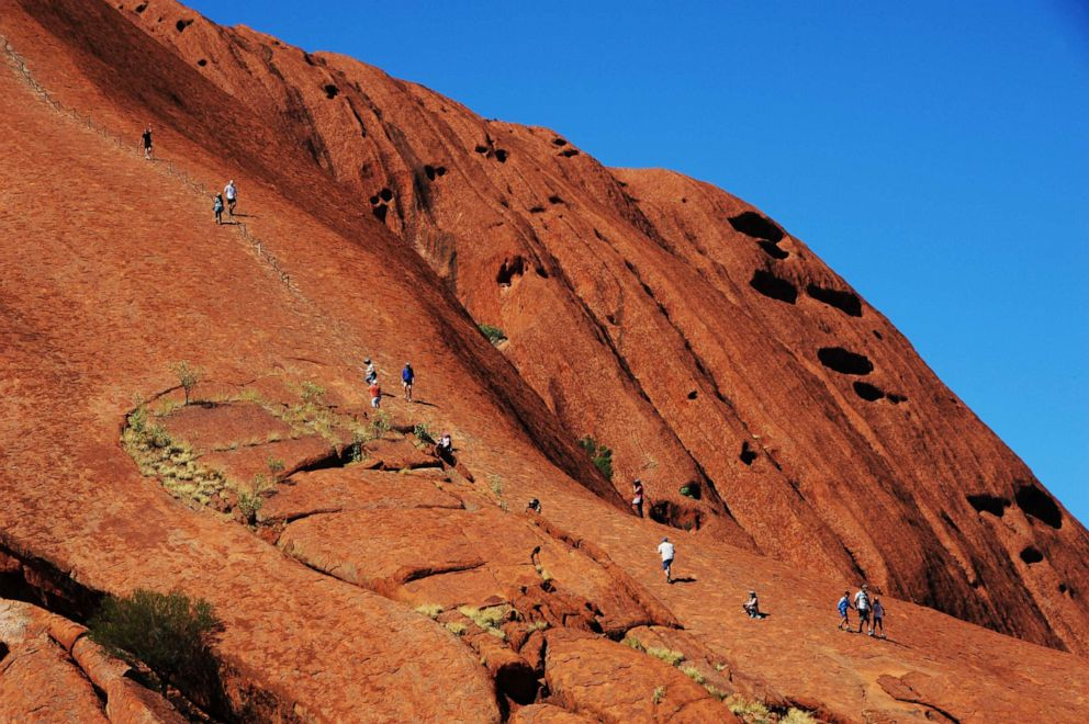 PHOTO: In this file photo, tourists climb on the rock formation of the Uluru in the Uluru Kata Tjuta National Park in Australia, April 15, 2018.