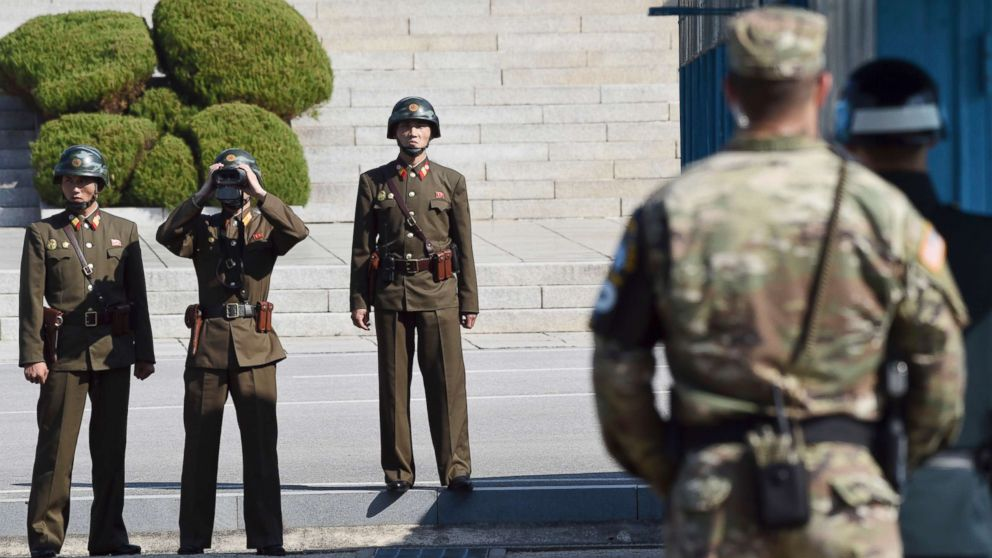 North Korean soldiers, left, look at the South side while U.S. Defense Secretary Jim Mattis and South Korean Defense Minister Song Young-moo visit the truce village of Panmunjom in the Demilitarized Zone (DMZ) on the border between North and South Korea, Oct. 27, 2017.