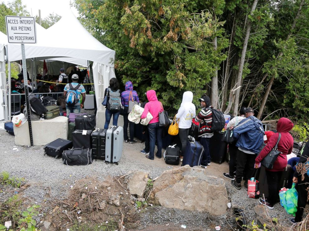 PHOTO: A line of asylum seekers who identified themselves as from Haiti wait to enter into Canada from Roxham Road in Champlain, New York, Aug. 7, 2017.