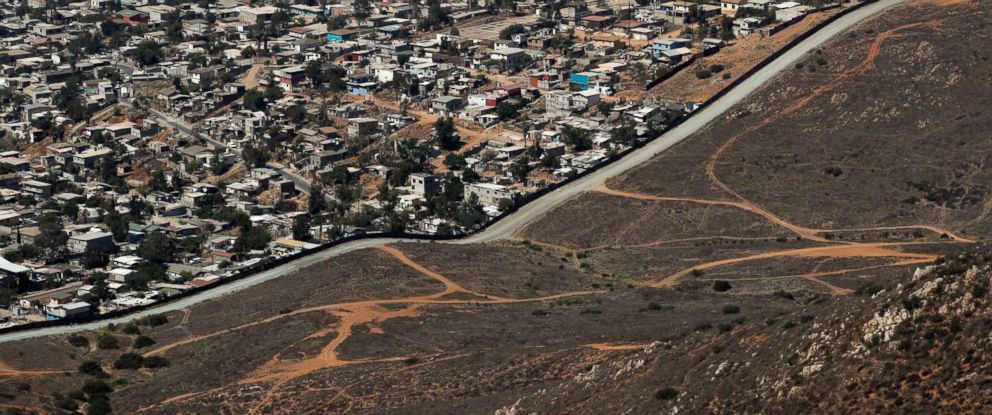 PHOTO: A road runs alongside a border wall that separates Tijuana, Mexico, top, from San Diego, June 28, 2018.