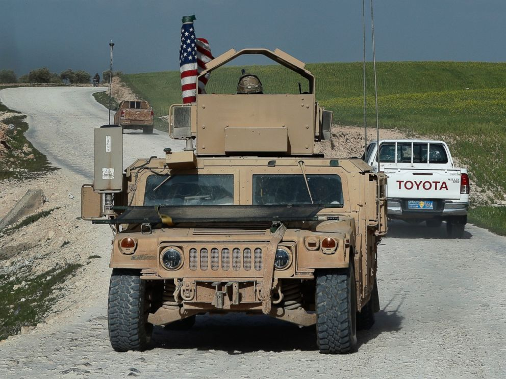In this picture taken on Thursday, March 29, 2018, U.S. troops humvee passes vehicles of fighters from the U.S-backed Syrian Manbij Military Council on a road leading to the tense front line with Turkish-backed fighters, north of Manbij town, Syria.