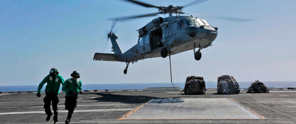 """This image released,May 10, 2019 shows a naval logistics specialists attaches cargo to an MH-60S Sea Hawk helicopter from the """"Nightdippers"""" of Helicopter Sea Combat Squadron 5 from the flight deck of the Nimitz-class aircraft carrier USS Abraham Lincoln."""