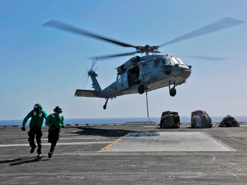 This image released,May 10, 2019 shows a naval logistics specialists attaches cargo to an MH-60S Sea Hawk helicopter from the Nightdippers of Helicopter Sea Combat Squadron 5 from the flight deck of the Nimitz-class aircraft carrier USS Abraham Lincoln.