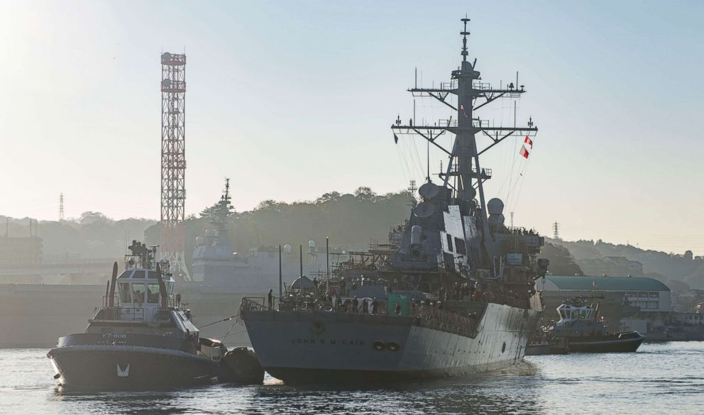 The guided missile destroyer USS John S. McCain is pulled towards a pier after departing from a dry dock at Fleet Activities Yokosuka in Japan, Nov. 27, 2018.