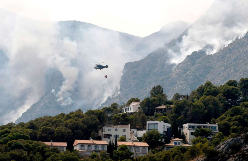 PHOTO: A helicopter drops water over a wildfire in Pinet, in the eastern Spanish region of Valencia, August 7, 2018.