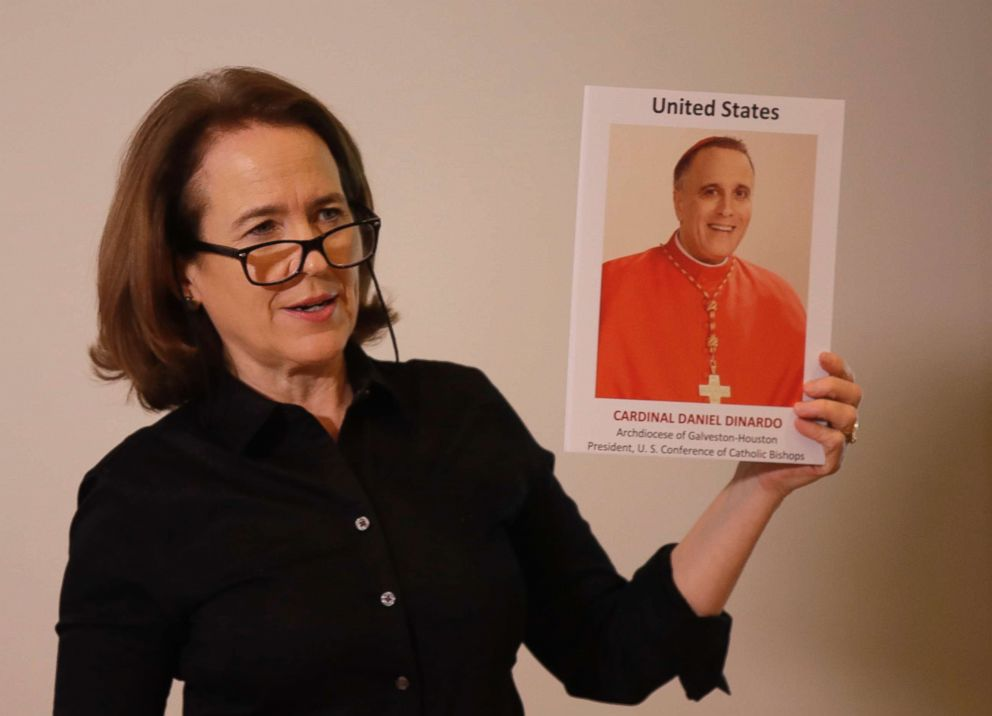 PHOTO: Anne Barrett Doyle, co-director of BishopAccountability.org group, holds up a photo of Cardinal Daniel DiNardo in Rome, Feb. 19, 2019.