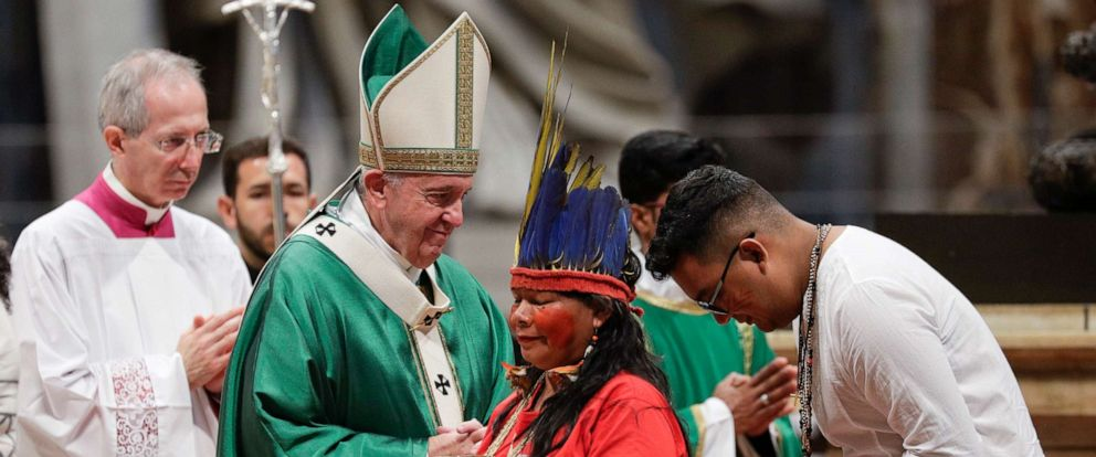 PHOTO: Indigenous peoples, some with their faces painted and wearing feathered headdresses, stand by Pope Francis as he celebrates an opening Mass for the Amazon synod, in St. Peters Basilica, at the Vatican, Oct. 6, 2019.