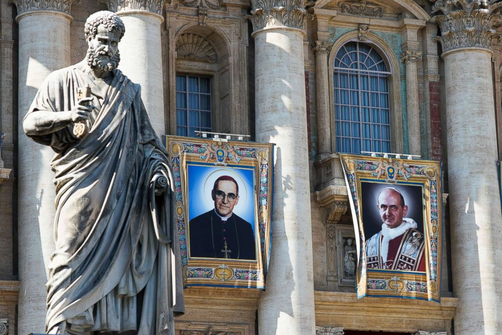 PHOTO: The tapestries of Roman Catholic Archbishop Oscar Romero, left, and Pope Paul VI hang from a balcony of the facade of St. Peters Basilica at the Vatican, Oct. 13, 2018.