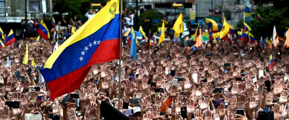PHOTO: People raise their hands during a mass opposition rally against President Nicolas Maduro in in Caracas, Venezuela, Jan. 23, 2019.