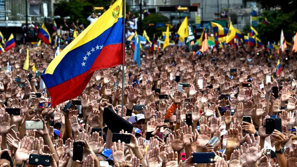 People raise their hands during a mass opposition rally against President Nicolas Maduro in in Caracas, Venezuela, Jan. 23, 2019.
