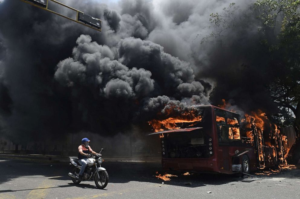PHOTO: An opposition demonstrator passes by a government bus set on fire during clashes with soldiers loyal to Venezuelan President Nicolas Maduro after troops joined opposition leader Juan Guaido in his campaign to oust Maduro in Caracas, April 30, 2019.