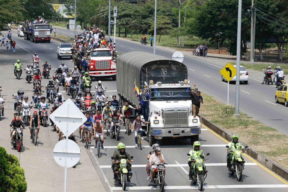 PHOTO: Venezuelans ride atop and alongside semi-trailers accompanying U.S. humanitarian aid destined for Venezuela, in Cucuta, Colombia, Feb. 23, 2019.