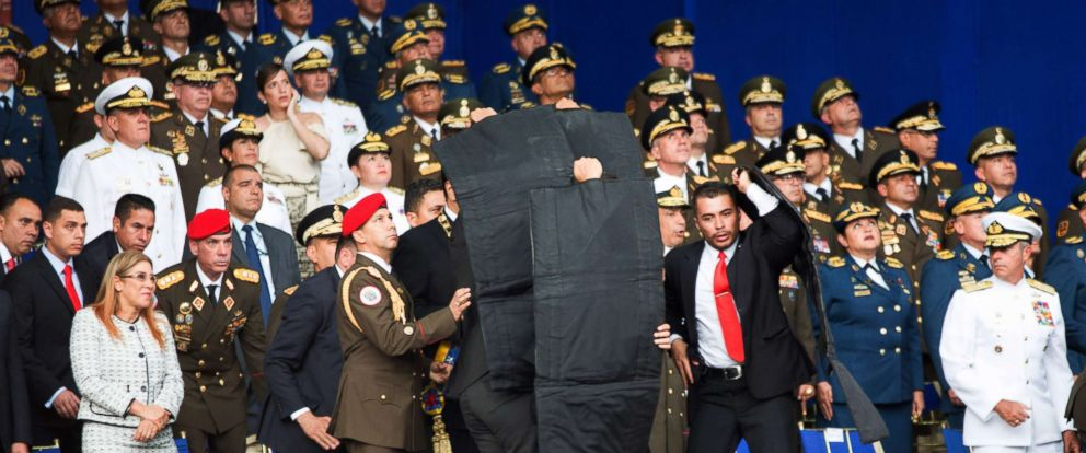 PHOTO: Security members surround and protect Venezuelan President Nicolas Maduro after his speech was interrupted in Caracas, Venezuela, on Aug. 4, 2018.