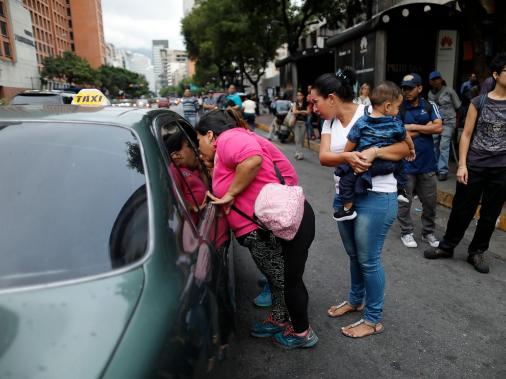 PHOTO: People ask a taxi driver how much it is to take them to their neighborhood during a blackout in Caracas, Venezuela, Monday, July 22, 2019.