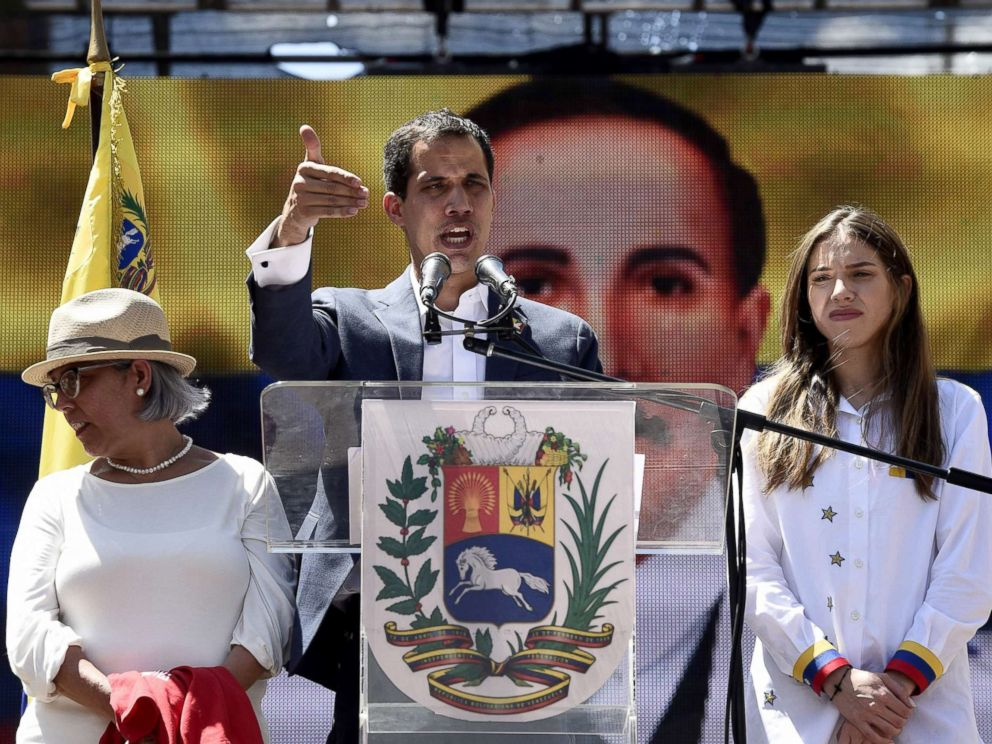 PHOTO: Venezuelan opposition leader and self declared acting president Juan Guaido, accompanied by his mother Norka Marquez, left, and wife Fabiana Rosales, speaks to supporters during a rally in Caracas, Feb. 12, 2019.