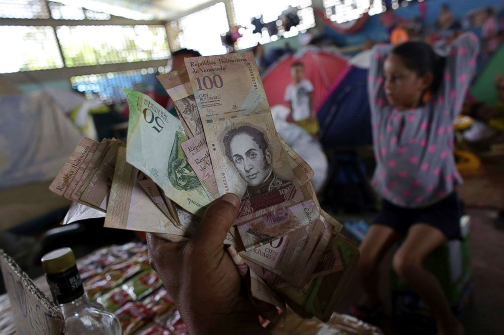 PHOTO: Venezuelan Charlie Ivan Delgado shows his countrys currency as he talks about the economic crisis at a migrant shelter inside the Tancredo Neves Gymnasium in Boa Vista, Roraima state, Brazil.